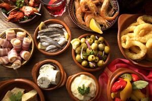 Griechische Spezialitäten auf einem Holztisch in Marmorschalen angerichtet.
