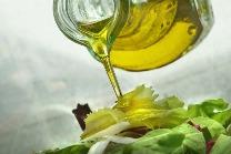 Olivenöl wird aus einer Karaffe auf Salat gegeben.