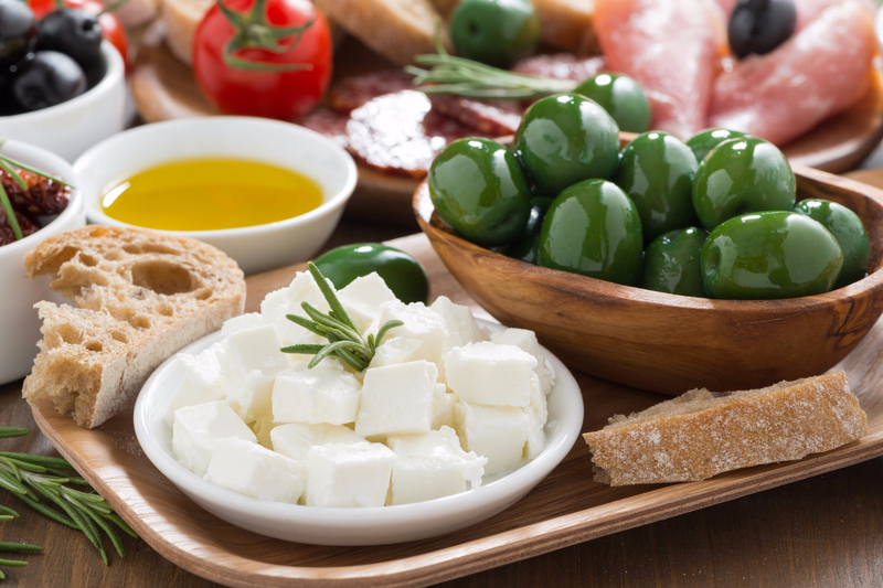 Food tray with bread, feta, olives and olive oil.