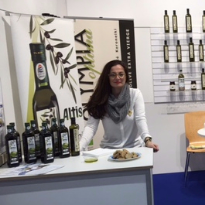 Maria Rotiri behind an exhibition stand, presenting Optima Feinkost's products